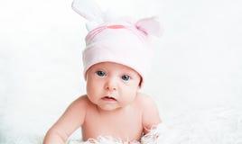Śliczna nowonarodzona dziewczynka w różowym kapeluszu z ucho Zdjęcia Stock