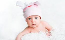 Śliczna nowonarodzona dziewczynka w różowym kapeluszu z ucho Zdjęcia Royalty Free