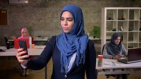 Śliczna opowiada kobieta w błękitnym hijab ma wideo wezwanie nad telefonem w ceglanym biurze w inny podczas gdy stojący i ono uśm