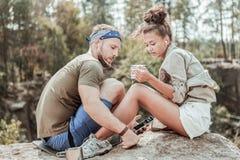 Śliczna para podróżnicy dzieli słuchawki podczas gdy słuchający muzyczny siedzący pobliski jezioro zdjęcia royalty free