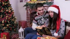 Śliczna para siedzi blisko choinki i inne dekoracje czyta książkę zdjęcie wideo