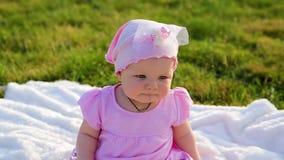 Śliczna piękna dziecięca dziewczyna w menchii ubraniach jest nerwowym obsiadaniem na białej koc kłaść na zielonej trawie w miasto zbiory