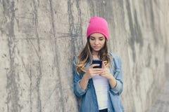 Śliczna piękna dziewczyna stoi blisko ściany na ulicie i używa jej smartphone dla komunikaci przez cały int w przypadkowych ubran obrazy royalty free