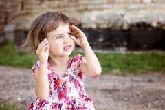 Śliczna piękna mała dziewczynka chuje jej twarz w ona ręki Fotografia Royalty Free