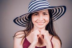 Śliczna powabna brunetki kobieta w pasiastych kapeluszy spojrzeniach szczęśliwie z uśmiechem w kamerze na szarym tle i Fotografia Royalty Free