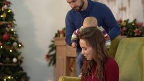 Śliczna powabna młoda kobieta czyta książkę dla męża i dziecka obsiadania w krześle obok choinki zbiory