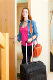 Śliczna pozytywna kobieta w cajgach z bagażem opuszcza dom Obrazy Royalty Free