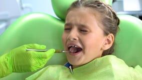 Śliczna preschool dziewczyna straszył stomatologiczny checkup z usta lustrem, dziecięcy strach zdjęcia stock