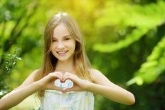 Śliczna preteen dziewczyna śmia się jej ręki w kierowym kształcie na letnim dniu i trzyma jaskrawym i pogodnym Śliczny dziecko on zdjęcia royalty free