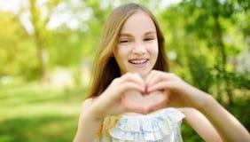Śliczna preteen dziewczyna śmia się jej ręki w kierowym kształcie na letnim dniu i trzyma jaskrawym i pogodnym Śliczny dziecko on obrazy stock