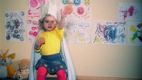 Śliczna princess dziewczyna z papierowym korony łasowania i obsiadania ciastkiem