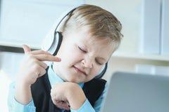 Śliczna 6 roczniaka chłopiec słucha muzyka lub audio tutorial na hełmofonach przy biurowym tłem w kostiumu obrazy stock