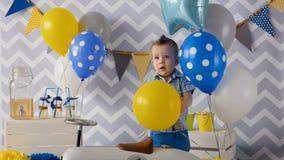 Śliczna 1 roku chłopiec świętuje jego jeden roku ` s urodziny z balonami zbiory