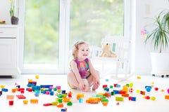 Śliczna roześmiana berbeć dziewczyna z kolorowymi blokami Fotografia Royalty Free