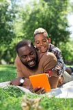 Śliczna rozochocona chłopiec patrzeje pastylka ekran zdjęcia royalty free