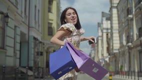 Śliczna rozochocona młoda kobieta z torbami na zakupy Dziewczyna tancząca z hełmofonami i telefonem komórkowym słucha muzyka podc zdjęcie wideo