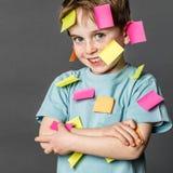 Śliczna ruchliwie chłopiec ono uśmiecha się z kleistymi notatkami all over obraz stock