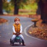 Śliczna rudzielec chłopiec jedzie pchnięcie samochód w jesień parku fotografia stock