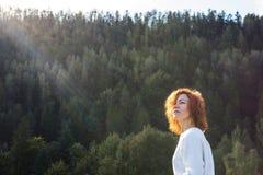 Śliczna rudzielec dziewczyna cieszy się słońce w lesie obraz stock