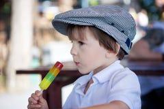 Śliczna słodka chłopiec, dziecko, je kolorowego lody w parku Obraz Stock