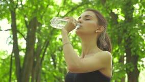 Śliczna sportowa dziewczyna bierze butelkę woda zbiory wideo