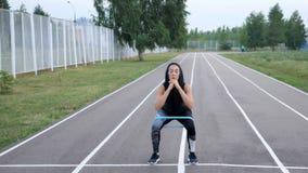 Śliczna sporty dziewczyna robi nóg ćwiczeniom z sprawność fizyczna gumowym zespołem plenerowym zbiory