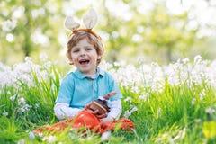 Śliczna szczęśliwa chłopiec jest ubranym Wielkanocnego królika ucho i je choco Obraz Stock