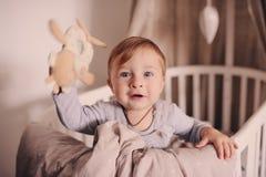 Śliczna szczęśliwa chłopiec obudzona w jego łóżku w bawić się i ranku Szczery zdobycz w prawdziwego życia wnętrzu Zdjęcie Stock
