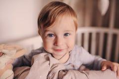 Śliczna szczęśliwa chłopiec obudzona w jego łóżku w bawić się i ranku Szczery zdobycz w prawdziwego życia wnętrzu Obrazy Stock