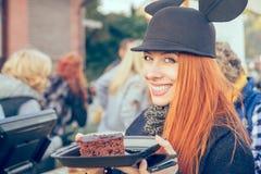 Śliczna szczęśliwa młoda kobieta w kapeluszowym łasowaniu tort outdoors obrazy royalty free