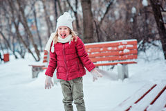 Śliczna szczęśliwa mała dziewczynka bawić się z śnieżnym i śmia się w zima parku Zdjęcia Stock