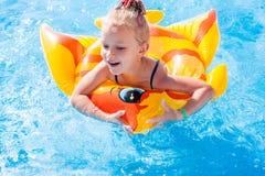Śliczna szczęśliwa mała dziewczynka ma zabawę w pływackim basenie Fotografia Royalty Free