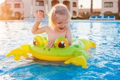 Śliczna szczęśliwa mała dziewczynka ma zabawę w pływackim basenie Obraz Royalty Free
