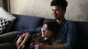 Śliczna szczęśliwa para młodzi modnisie kłama na leżance, śmia się podczas gdy watchingsomething na TV Wolny czas, cieszy się zbiory wideo