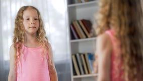 Śliczna szkolna dziewczyna w menchiach ubiera pozycję przed lustrem, dzieciństwo moda zdjęcie stock
