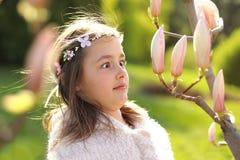 Śliczna tween dziewczyna z z handmade wiankiem na głowie z śmiesznej twarzy wyrażeniowy patrzeć zaskakująco przy magnoliowymi drz obrazy royalty free