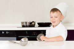 Śliczna uśmiechający się chłopiec w szefowie kuchni kapelusz i fartuch zdjęcie stock