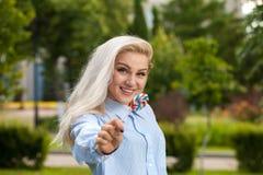Śliczna uśmiechnięta blondynka trzyma barwionego lizaka Zdjęcia Stock