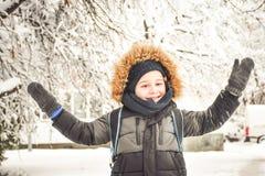 Śliczna uśmiechnięta chłopiec bawić się z śniegiem Fotografia Stock