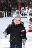 Śliczna uśmiechnięta chłopiec bawić się z śniegiem Zdjęcia Royalty Free