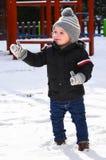 Śliczna uśmiechnięta chłopiec bawić się z śniegiem Obraz Stock