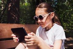 Śliczna uśmiechnięta dziewczyna siedzi na ławce w białej koszulce z mobilnym gadżetem w rękach Zdjęcia Royalty Free