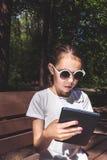 Śliczna uśmiechnięta dziewczyna siedzi na ławce w białej koszulce z mobilnym gadżetem w rękach Obraz Stock