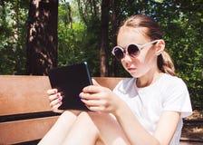 Śliczna uśmiechnięta dziewczyna siedzi na ławce w białej koszulce z mobilnym gadżetem w rękach Zdjęcia Stock