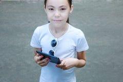 Śliczna uśmiechnięta dziewczyna w białej koszulce z mobilnym gadżetem w rękach Fotografia Stock