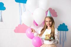 śliczna uśmiechnięta dziewczyna w partyjnego kapeluszowego mienia urodzinowym torcie i balonach podczas gdy patrzejący Fotografia Stock