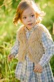 Śliczna uśmiechnięta dziewczyna w zielonym polu w zmierzchu Fotografia Stock