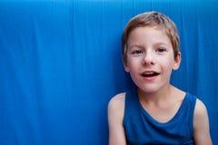 Śliczna uśmiechnięta młoda chłopiec z niebieskimi oczami na błękitnym tle Zdziwienie emocj projekt z kopii przestrzenią zdjęcie stock