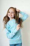 Śliczna uśmiechnięta mała dziewczynka czesze jej włosianą gręplę robi włosy zdjęcia royalty free