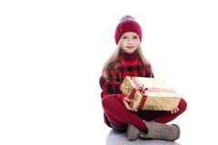 Śliczna uśmiechnięta mała dziewczynka jest ubranym z kędzierzawą fryzurą trykotowego puloweru, szalika i kapeluszu mienia bożych  zdjęcia royalty free